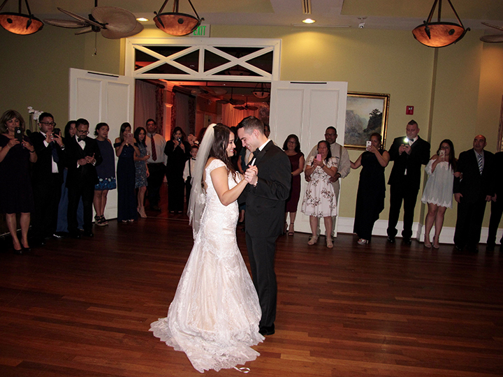 bride and groom on dance floor for their first dance in the ballroom