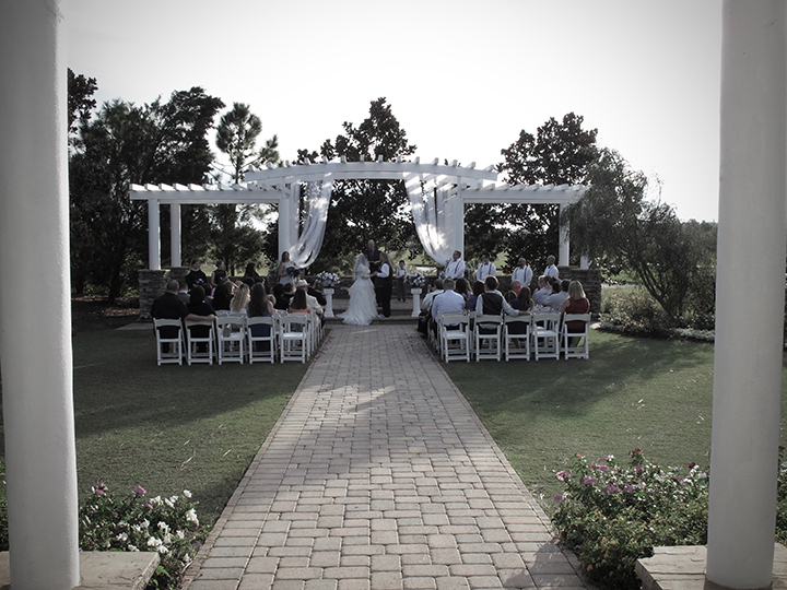 Outside wedding ceremony under the arbor at the St Cloud Royal Crest Room