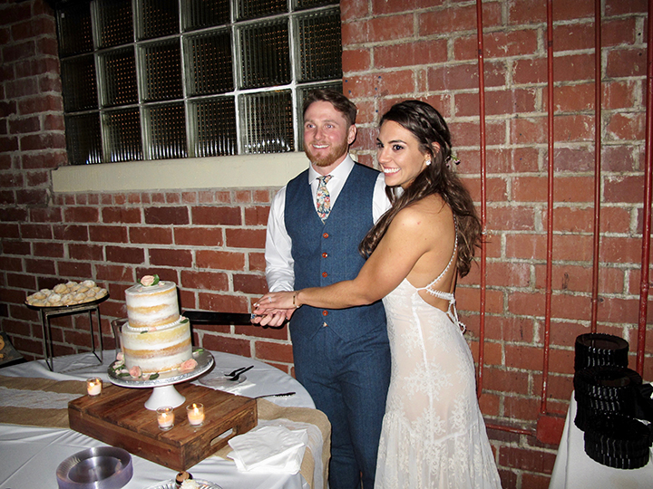 The couple cuts the cake from the 4 Rivers Sweet Shop