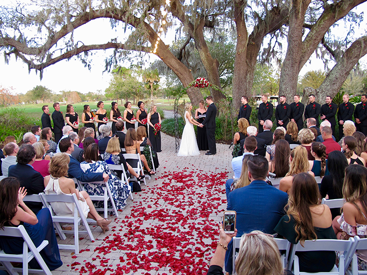 A wedding couple exchanges vows at their ceremony under the historic Oak Tree.