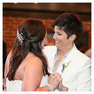 A same-sex LGBT couple share their first dance at their wedding reception at the Winter Park Farmer's Market