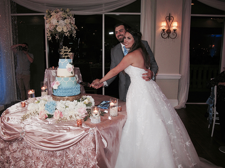 The bride and groom cut their wedding cake at their reception in the Crystal Ballroom Sunset Harbor.