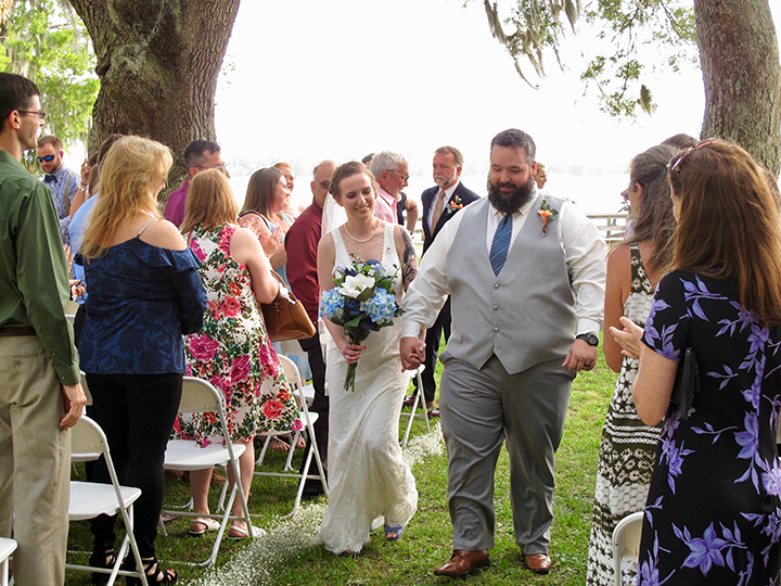 """The bride and groom walk down the aisle just after saying """"I do"""" at their ceremony next to the lake."""