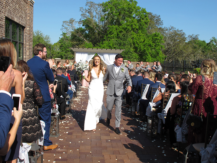 """The bride and groom walk back down the aisle after saying """"I Do"""" at the NOAH's Event Venue."""
