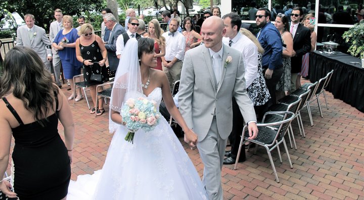 After exchanging their vows, a wedding couple exit their ceremony on the patio of 310 Lakeside.