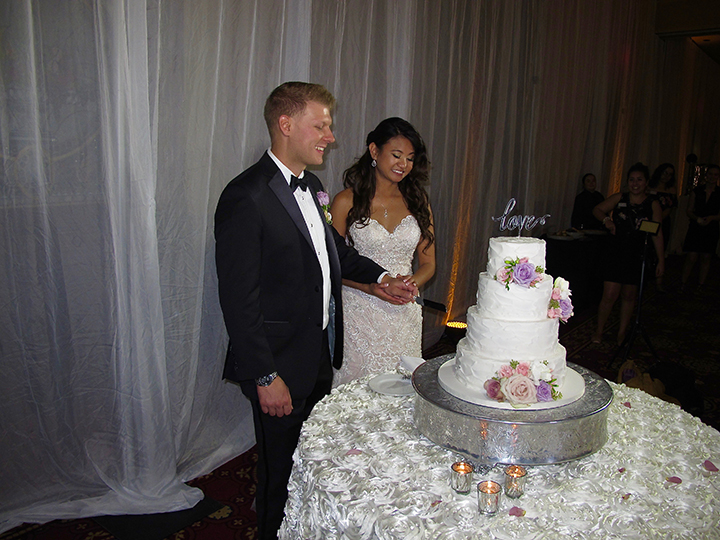 Wedding couple cutting the cake- at their reception at the Ballroom at Church Street in Downtown Orlando.