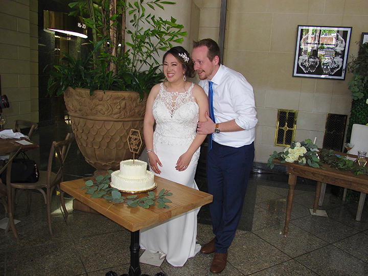 The bride and groom are cutting their wedding cake during their reception at the Dovecote Brasserie.