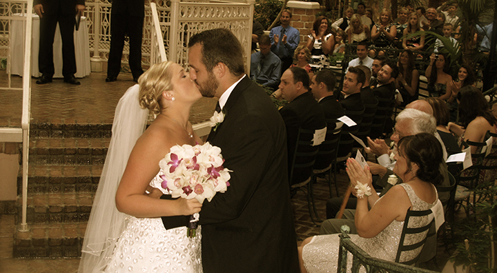 Just after a wedding ceremony, the couple share a kiss outside the gazebo.
