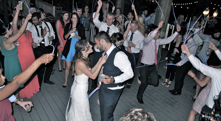 Wedding guests use glow sticks to close out the reception at Paradise Cove.