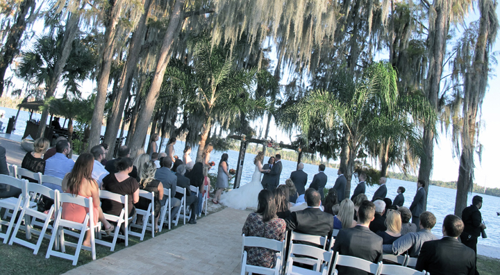 A wedding ceremony takes place underneath the cypress trees at Paradise Cove in Orlando.