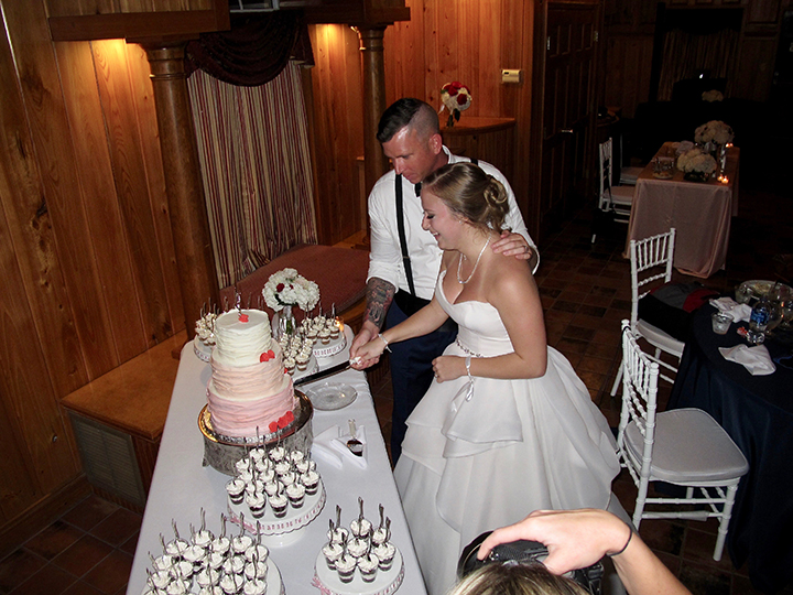 A Port Orange Wedding Couple celebrate by cutting the cake at the Estate on the Halifax.