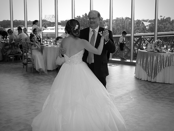 The Bride dances with her dad at her wedding reception in the GM Lounge at Epcot in Walt Disney World.