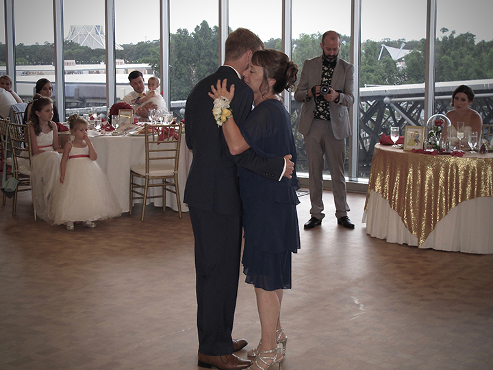 The groom dancing with his mom at his wedding at the Test Track VIP GM Lounge in Epcot.