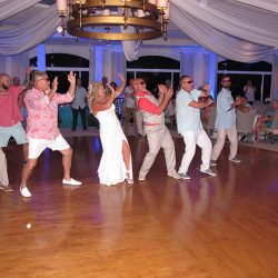 The bride and groom get a little crazy on the dance floor with Orlando DJ Chuck Johnson at the Hammock Dunes Club.
