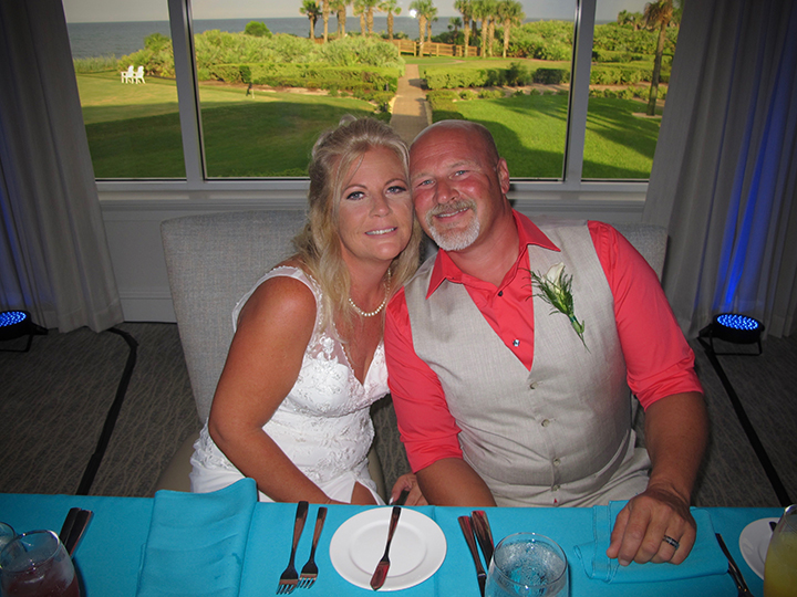 The wedding couple is seated at their sweetheart table at the Hammock Dunes Club in Palm Coast.