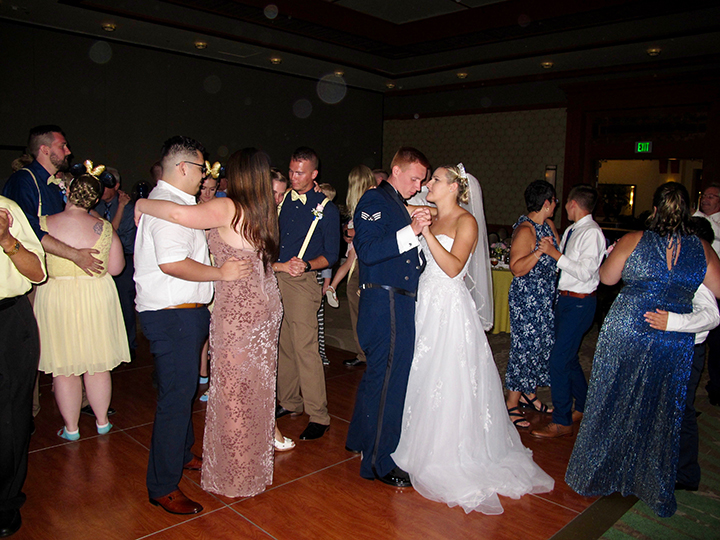 The wedding couple share a dance with family and friends during their reception.