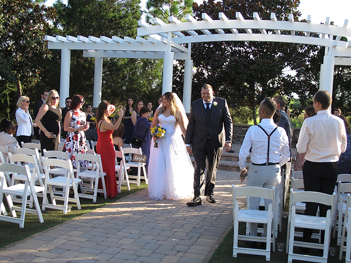"The couple walk down the aisle after saying ""I do"" at a Royal Crest Room Wedding."