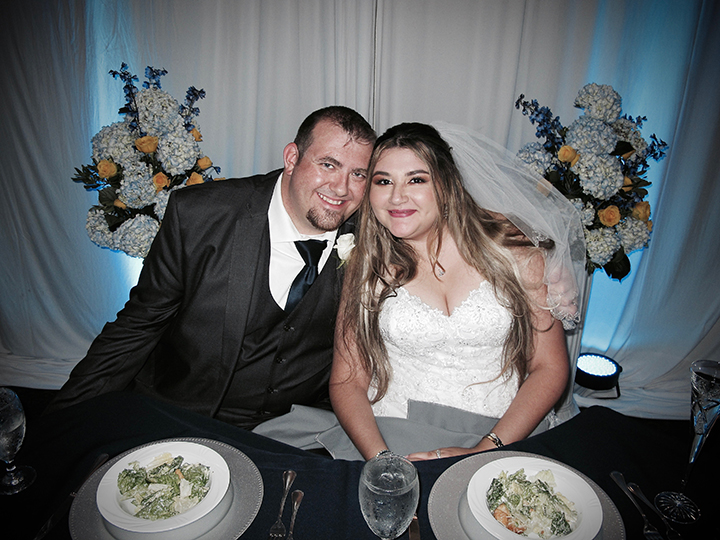 The Bride and Groom at their sweetheart table during their reception with Orlando DJ Chuck Johnson.