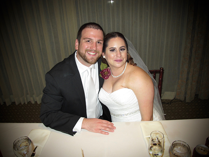 The bride and groom at their sweetheart table with Orlando Wedding DJ Chuck Johnson.