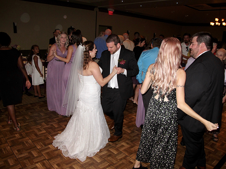 Guests are dancing with the bride and groom at their reception at Falcon's Fire Weddings.