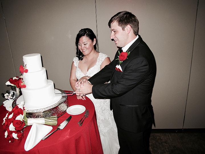 Cutting the cake at the reception with Orlando Wedding DJ Chuck Johnson.