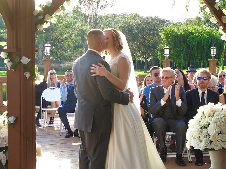 "The couple exchanging a kiss after saying ""I do"" at a Shades of Green Wedding."
