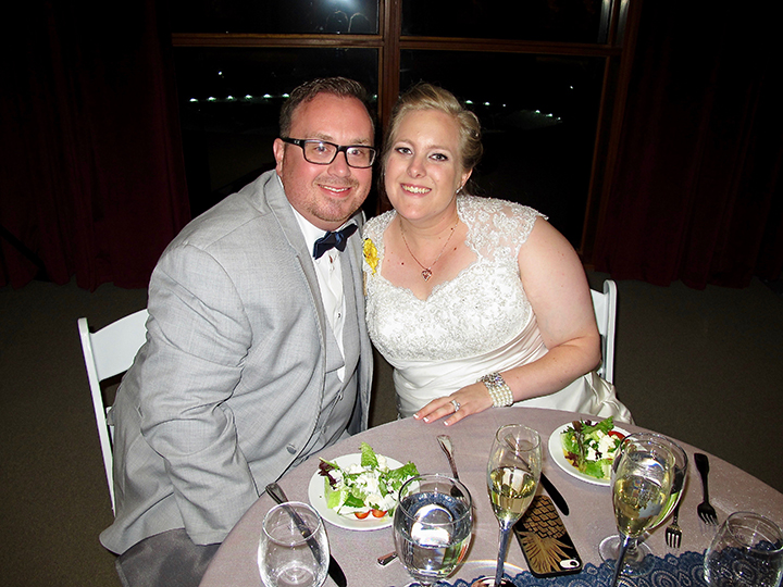 The wedding couple at their sweetheart table at a St Augustine's World Golf Hall of Fame wedding.