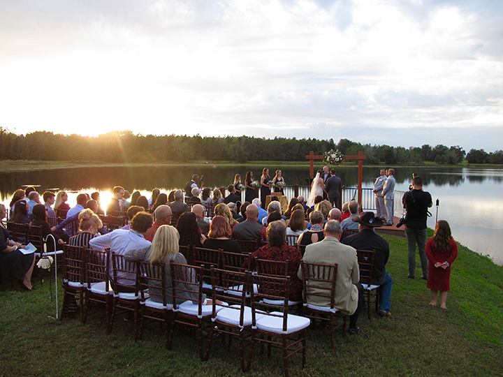The sun sets over the lake at the ceremony at Skyline Ranch Weddings.