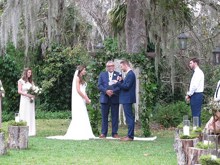 The couple exchange their vows at an outside wedding ceremony at the Mulberry at New Smyrna Beach.