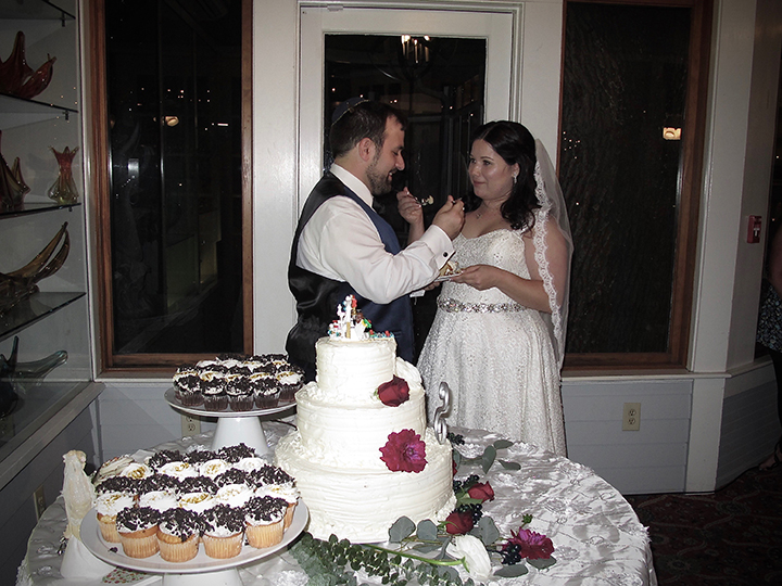 The bride and groom cut the cake at their wedding at the Courtyard at Lake Lucerne