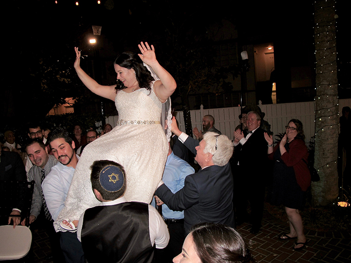 The bride is lifted on her chair during the Hora Dance at the Courtyard at Lake Lucerne