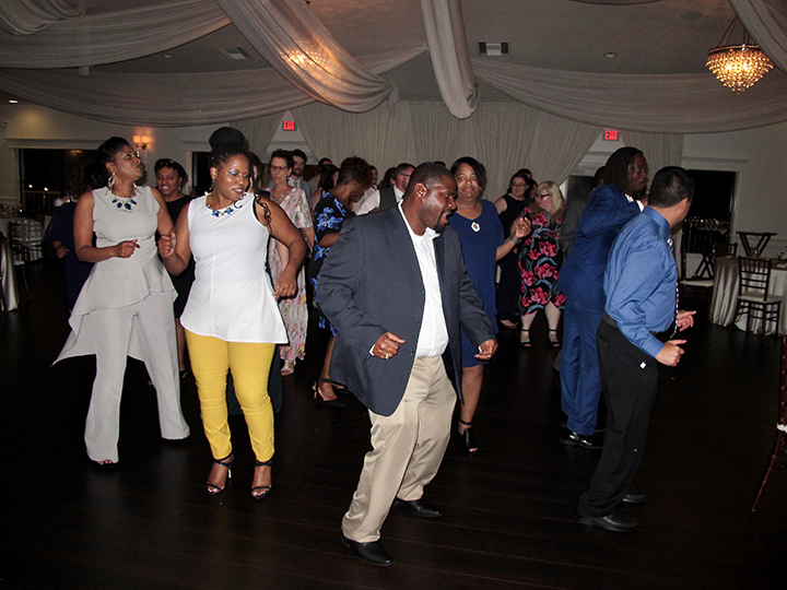 Friends and family join the wedding couple on the dance floor at the Royal Crest Room.