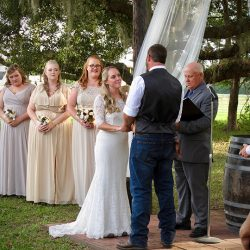 A wedding ceremony takes place outside at the Red Barn at Bushnell.