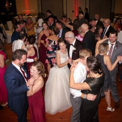 The bride and groom with family and friends on the dance floor with WDW Swan Hotel weddings.